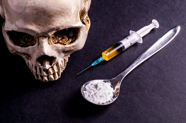 Drug paraphernalia and a skull showing the results of taking dtrugs and being addicted.